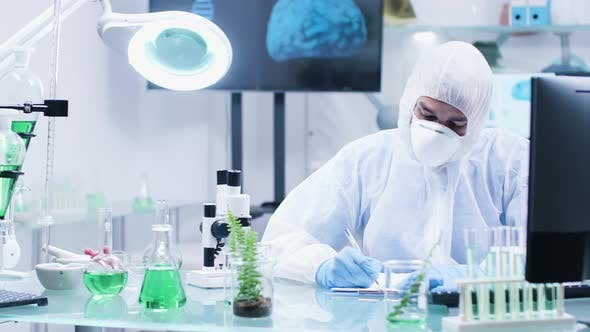 Thumbnail for In High-end Biochemistry Laboratory a Scientist in Coveralls Is Making Notes