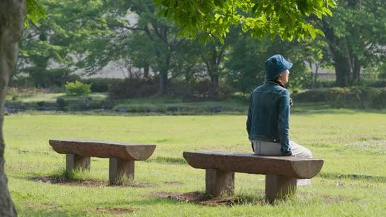 Thumbnail for Woman sit on the wooden bench and look around in the park