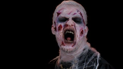 Creepy Man with Halloween Zombie Undead Bloody Wounded Makeup Trying to Scare Face Expressions
