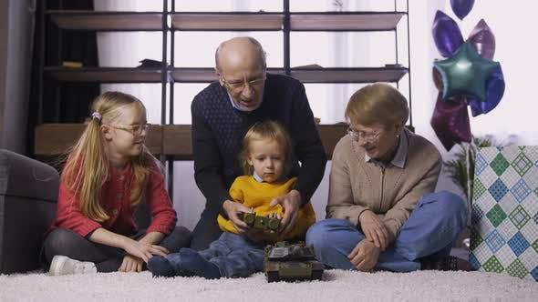 Thumbnail for Granfather Teaching Boy To Use Radio Control Toy