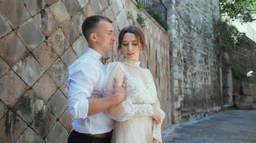 Romantic wedding couple standing and walking in old town in Montenegro.