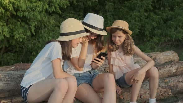 Cover Image for Group of Children, Three Girls Sitting on Logs in Nature Looking at Smartphone