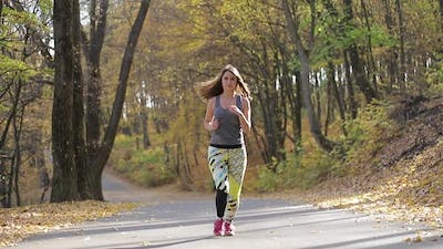 Girl running in the morning Park, workout. European sports fitness model in sports running clothes.