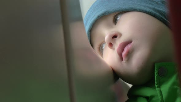 Thumbnail for Close Up View of Small Boy Bored Face in Winter Hat on His Place in the Rail Train