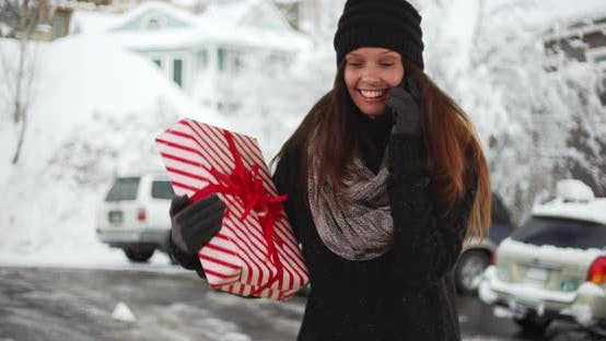 Thumbnail for Woman talking on cellphone while holding Christmas gift in snowy parking lot
