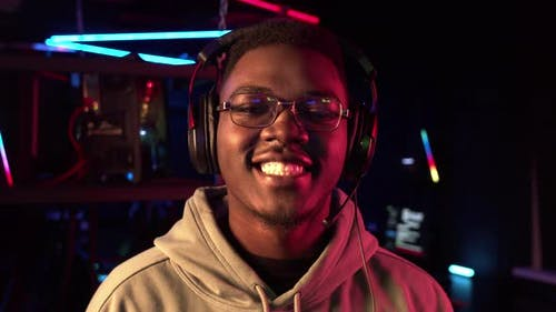 A Closeup Portrait of a Cute Black Student Wearing Glasses and Headphones Smiling at the Camera