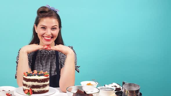 Thumbnail for Happy Girl Pastry Chef Smiling at Camera While Sitting at the Table with Pastry
