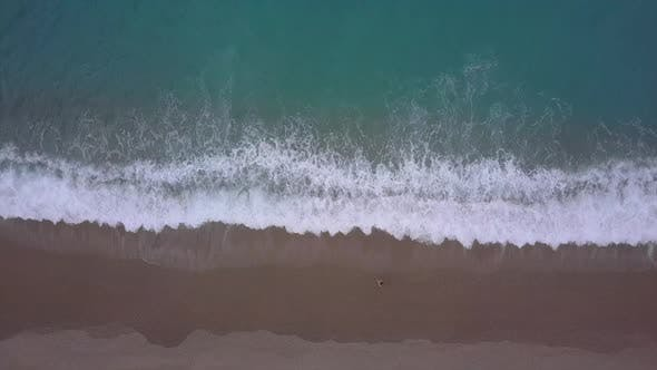 Cover Image for Aerial top view turquoise waves break on empty pebble beach. Pure calm sea from bird's eye view