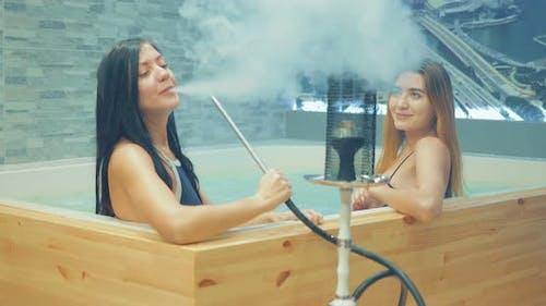 Beautiful and Sexy Girls Smoke Hookah in the Jacuzzi
