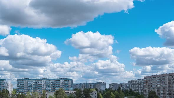 Thumbnail for Cumulus Cirrus Clouds Move in the Blue Sky Over Multi-story Buildings in City