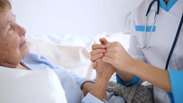 Elderly Health Care. Doctor Reassuring Senior Patient. Medical Staff At Home.