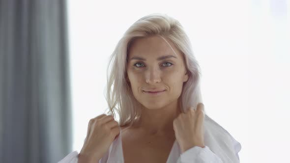 Thumbnail for Attractive Young Blonde Putting on White Shirt by Window