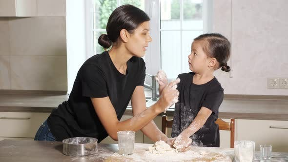 Lovely Daughter and Mother Play with Flour and Dough
