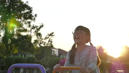 Girl Riding Seesaw Board With Big Smile And Happy Face
