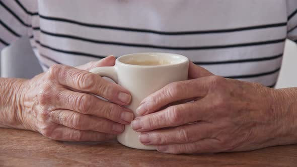 Thumbnail for Close up on senior Caucasian womans hands on coffee cup at wood table