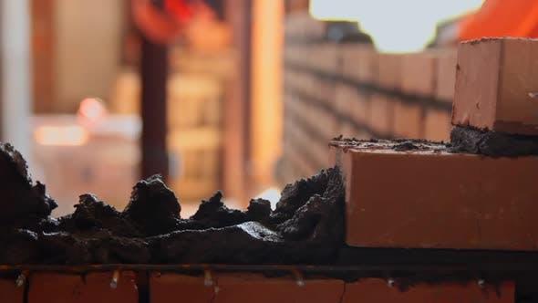 Thumbnail for Mason makes a wall of red brick
