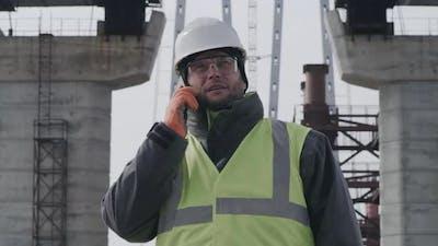 Male Engineer Examining Bridge and Speaking on Cellphone