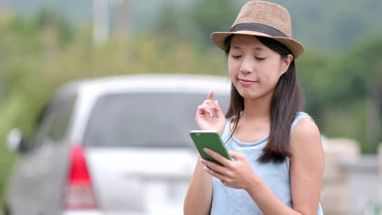 Travel woman think of the location of destination on cellphone map between road trip