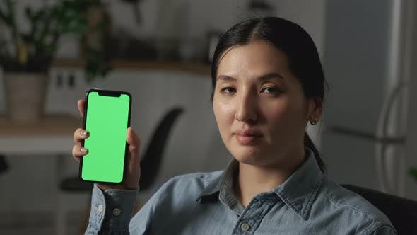 Young happy beautiful multi-ethnic woman showing phone with green screen