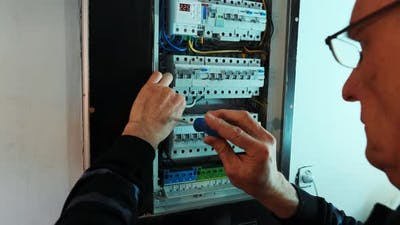 Electricians hands working on current  electric in control panel.