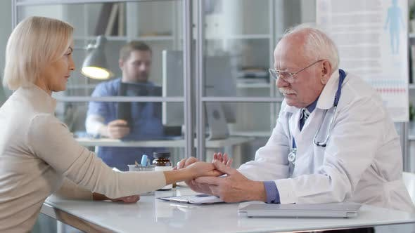 Senior Doctor Checking Pulse at Wrist of Female Patient