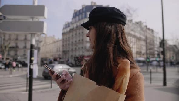 Thumbnail for Glückliche schöne junge Bloggerfrau umschauen zu posten Online mit Smartphone bei Sunny Paris