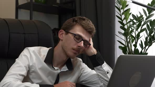 Thumbnail for Sleeping man in eyeglasses is trying to work in business office