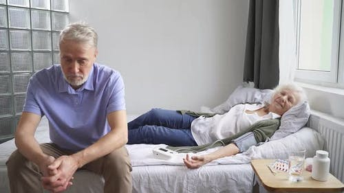 Caucasian Elderly Woman Lies on a Bed with High Blood Pressure and Her Husband Sits Next To Her and