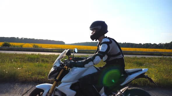 Thumbnail for Man in Helmet Riding Fast on Sport Motorbike Along Highway with Scenic View at Background