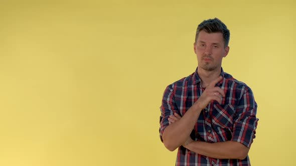 Thumbnail for On Yellow Background Cheerful Tall Boy Making a Hush Gesture.