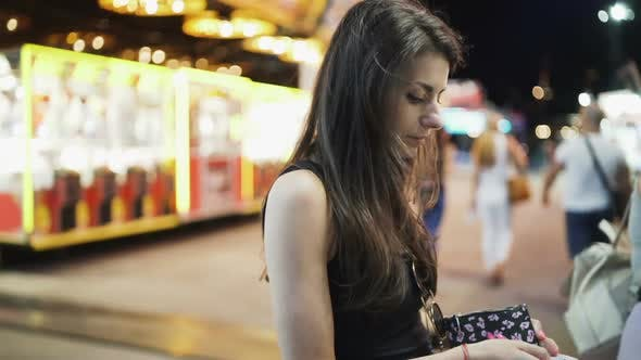Brunette Woman Counting Cash, Waiting on the Line To Buy Carnival Tickets