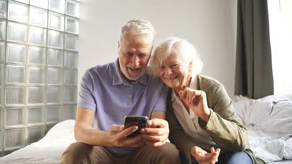 Happy Elderly Couple Using Their Smartphone Make a Video Call with Friends and Family