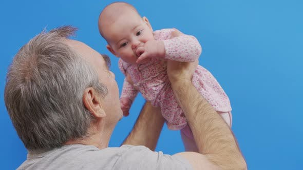Funny Game and Laugh of Caucasian Old Man and Baby Girl in Domestic Comfort. Wrinkled Skin of