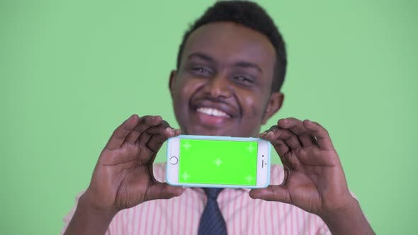 Face of Happy Young African Businessman Showing Phone