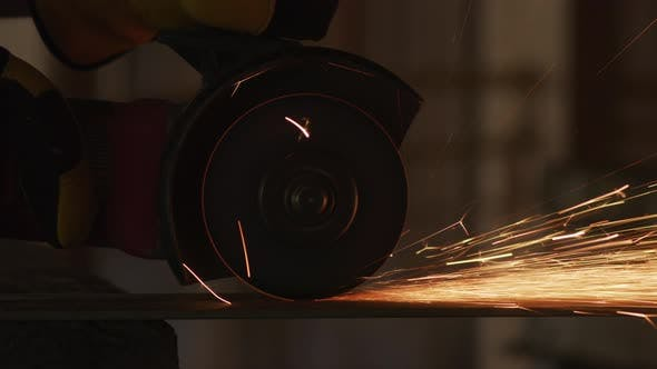 Thumbnail for Construction worker grinding metal and making sparks, closeup