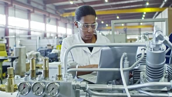 Thumbnail for African Female Engineer Operating Industrial Machine with Laptop