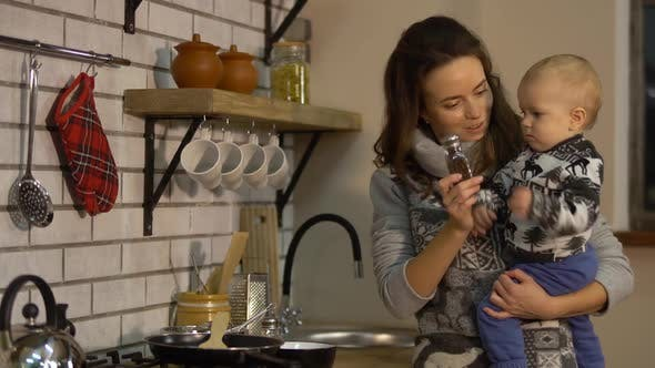 Thumbnail for Pretty Young Woman with a Baby in Her Arms in Modern Kitchen Preparing Breakfast