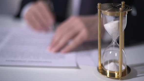 Closeup of Sand Clock Measuring Time, Businessman Signing Important Contract