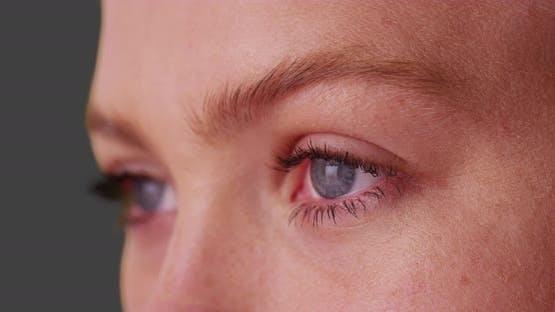 Nahaufnahme der schönen Frau mit blauen Augen auf grauem Hintergrund.