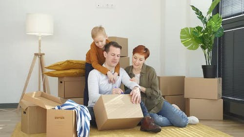Young Caucasian Family Moving to New Place Sitting Holding Marker Pen Writing Carboard Boxes