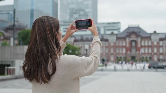 Thumbnail for Woman use of mobile phone to take photo in Tokyo station