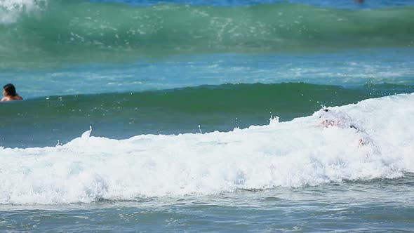 Ocean Wave Taking Young Male on Surfing Board Back Closer to Seashore, Sport