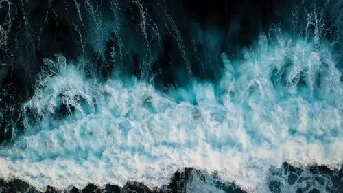 Above vertical view of blue ocean waves and black rocks coast - summer holiday vacation