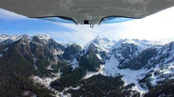 Cover Image for Helicopter Approaching Mountain Range After First Snow Above Trees In Cascades