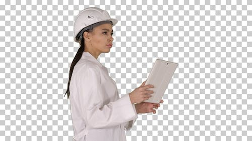Young woman engineer walking with tablet looking at objects