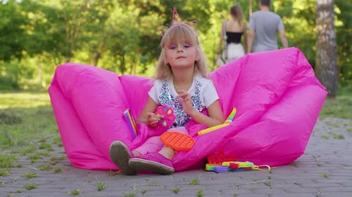 Joyful Girl Playing Spinning with Pop It Sensory Antistress Toy in Park Stress Anxiety Relief