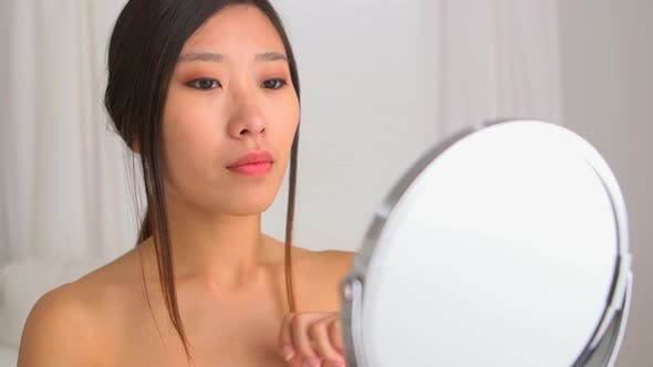 Thumbnail for Asian woman fixing her hair