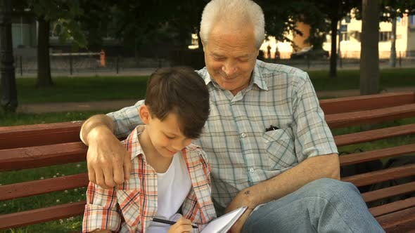 Thumbnail for Little Boy Writes in His Notebook What His Grandpa Says
