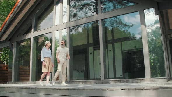 Upper-Class Senior People Walking before Vacation Home