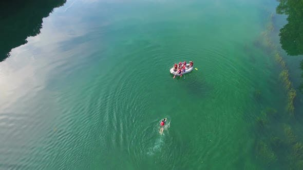 Thumbnail for Aerial view of rafter swimming to boat after falling from it